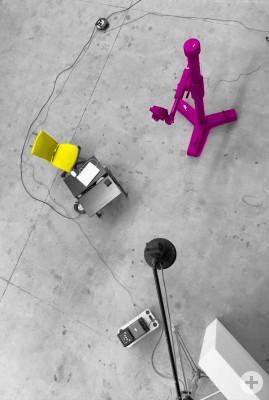 Ein aufgeräumtes Studio von oben. Zu sehen ist ein Stativ, ein Computertisch und eine Blitzleuchte.